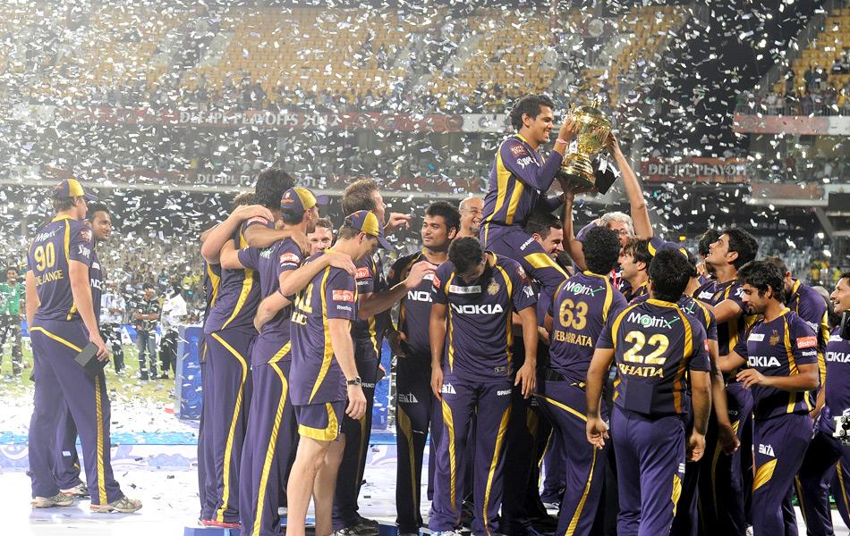 Kolkata Knight Riders cricketers, support staffs and officials celebrate with the DLF IPL trophy after winning the IPL Twenty20 cricket final match between Chennai Super Kings and Kolkata Knight Riders at the M.A.Chidambaram Stadium in Chennai on May 27, 2012.   AFP PHOTO/Dibyangshu SARKAR