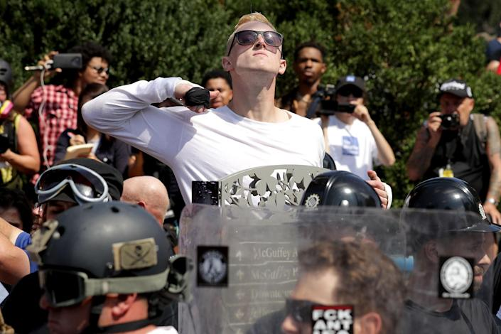 <p>A man makes a slashing motion across his throat twoard counter-protesters as he marches with other white nationalists, neo-Nazis and members of the 'alt-right' during the 'Unite the Right' rally August 12, 2017 in Charlottesville, Virginia. After clashes with anti-fascist protesters and police the rally was declared an unlawful gathering and people were forced out of Lee Park, where a statue of Confederate General Robert E. Lee is slated to be removed. (Photo: Chip Somodevilla/Getty Images) </p>
