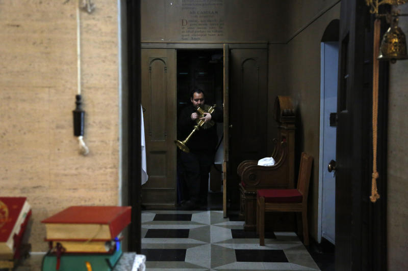 In this April 19, 2020, photo, the Rev. Joseph Dutan prepares for a virtual holy hour livestreamed for the parishioners of St. Brigid Church in the Brooklyn borough of New York. The harm caused by the coronavirus is all around him: The funeral home across from St. Brigid, always busy. (AP Photo/Jessie Wardarski)