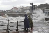 People watch as waves crash along the coast at Swanage in Dorset. Parts of the UK are preparing to be lashed by heavy rain and high winds as Storm Alex heralds the arrival of a stretch of bad weather over the weekend.