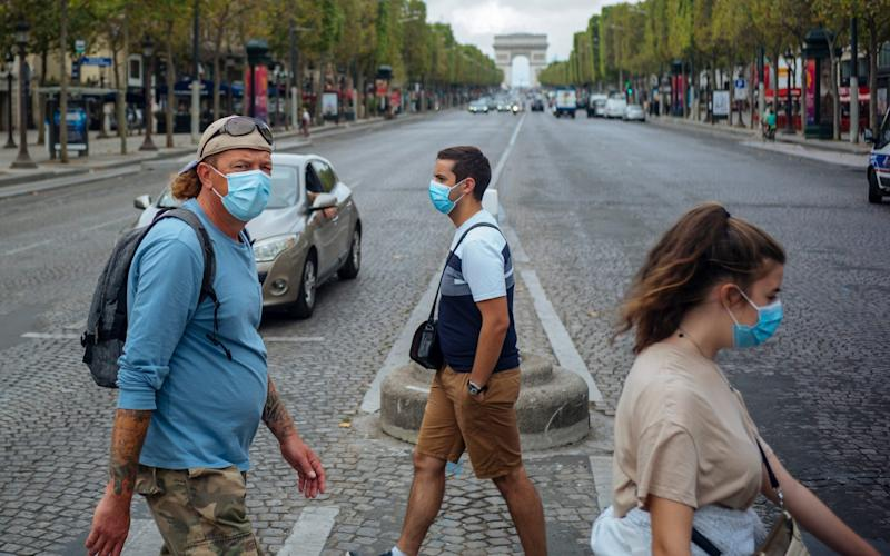 People with face masks cross the Champs Elysee - AP Photo/Kamil Zihnioglu
