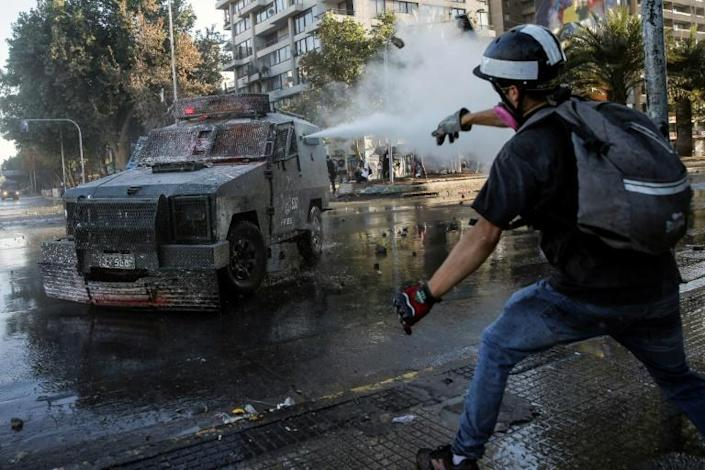Riot police deployed armored water cannons to disperse the Santiago demonstrators (AFP Photo/JAVIER TORRES)