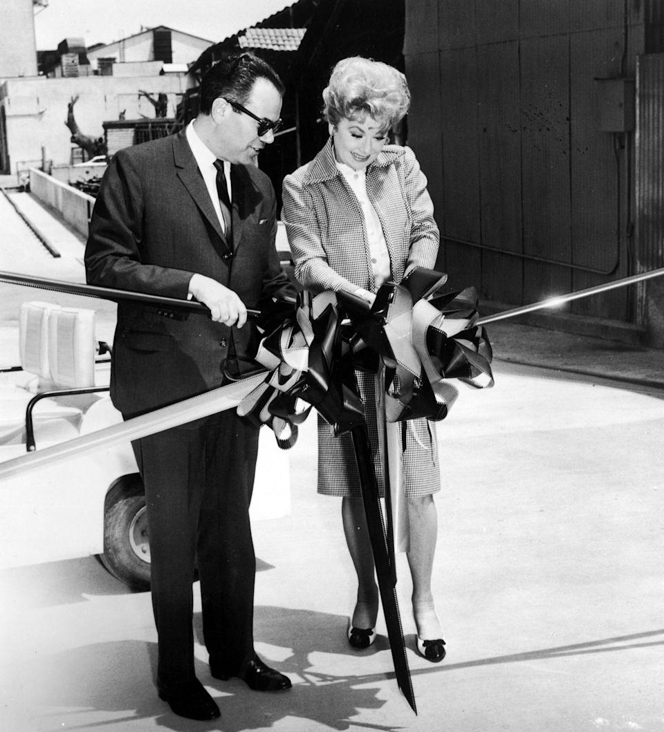 <p>Lucille Ball cuts the ribbon at the ceremony celebrating the acquisition of her production company Desilu Productions, circa 1967.</p>