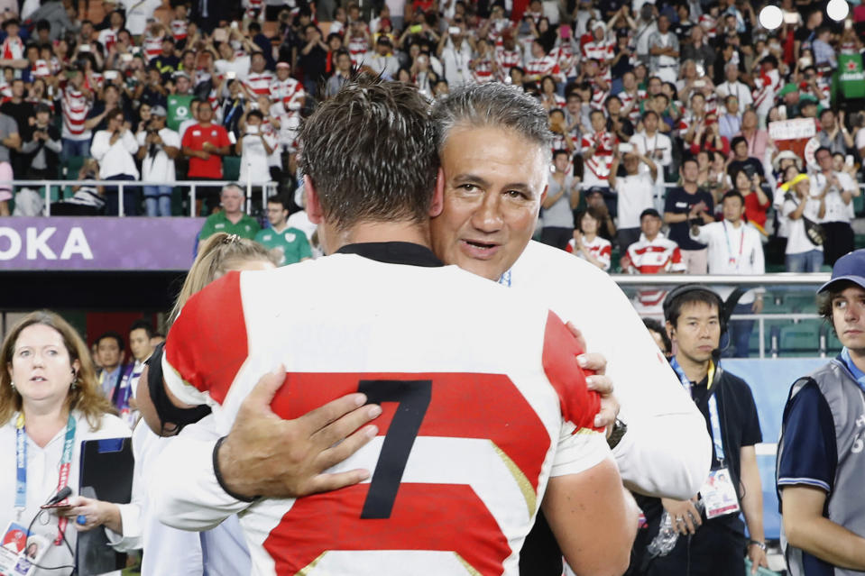 Japan's head coach Jamie Joseph, right, hugs captain Pieter Labuschagne after winning over Ireland during the Rugby World Cup Pool A game at Shizuoka Stadium Ecopa between Japan and Ireland in Shizuoka, Japan, Saturday, Sept. 28, 2019. (Kyodo News via AP)