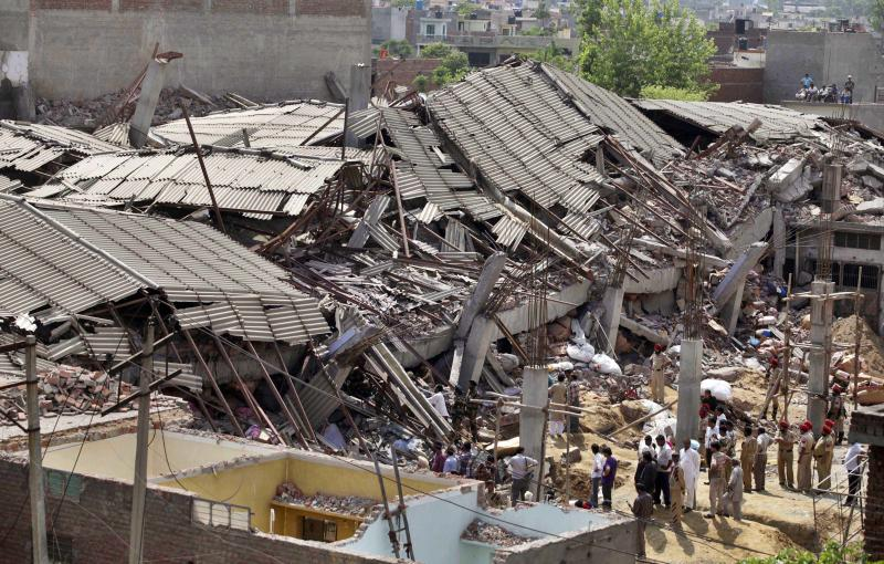 Rescue workers and Indian army soldiers search through the debris of a collapsed factory during a rescue operation in Jalandhar, India, Monday, April 16, 2012. Several people are feared to be trapped after a three-story building of a factory collapsed after a blast in the factory's boiler, according to local reports. (AP Photo/Altaf Qadri)