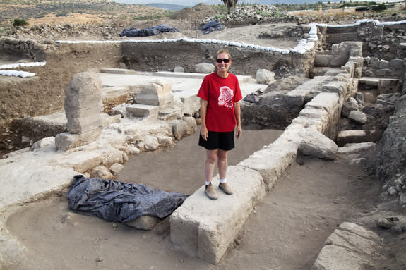Archaeological dig leader Jodi Magness standing on a wall within the excavation site.