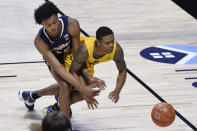 Virginia's Trey Murphy III, left, and San Francisco's Khalil Shabazz, chase a loose ball in the second half of an NCAA college basketball game, Friday, Nov. 27, 2020, in Uncasville, Conn. (AP Photo/Jessica Hill)