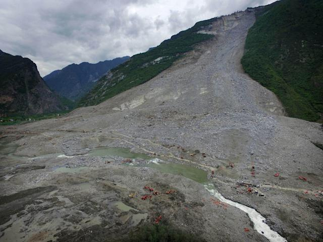 <p>Chinese rescuers search for survivors at a landslide area in the village of Xinmo in Maoxian county, China's Sichuan province on June 25, 2017. <br>Rescuers dug through earth and rocks for a second day on June 25 in an increasingly bleak search for some 118 people still missing after their village in southwest China vanished under a huge landslide. Officials have pulled 15 bodies from the avalanche of rocks that crashed into 62 homes in Xinmo, a once picturesque mountain village nestled by a river in Sichuan province. (Photo: STR/AFP/Getty Images) </p>