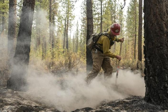 Firefighter Garrett Suza, with the Chiloquin Forest Service, mops up a hot spot on the North East side of the Bootleg Fire, Wednesday, July 14, 2021, near Sprague River, Ore. (AP Photo/Nathan Howard)