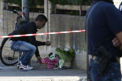A man places flowers on the site of a blast near a school in Brindisi