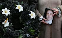 <p>Marie Lynskey holds a photograph of her uncle Joe Lynskey, one of the disappeared, during the 11th annual 'Silent Walk for the Disappeared' to remember victims of Northern Ireland's Troubles at Stormont, Belfast. (AP) </p>