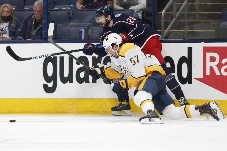 Columbus Blue Jackets' Oliver Bjorkstrand, top, passes the puck as Nashville Predators' Dante Fabbro defends during the second period of an NHL hockey game Wednesday, May 5, 2021, in Columbus, Ohio. (AP Photo/Jay LaPrete)
