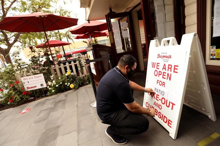 """Martin Tario, who co-owns Dupar's Restaurant with his wife Frances, replaces """"dine-in"""" with """"patio"""" at his restaurant at the Original Farmers Market. California Governor Gavin Newsom ordered indoor restaurants closed effective immediately on July 1. <span class=""""copyright"""">(Genaro Molina / Los Angeles Times)</span>"""