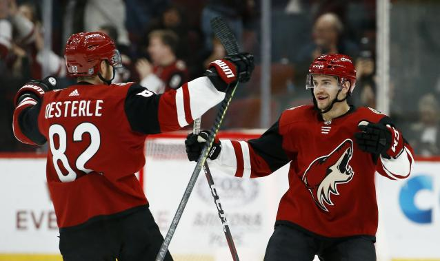 Arizona Coyotes center Vinnie Hinostroza, right, celebrates his goal against the Florida Panthers with Coyotes defenseman Jordan Oesterle (82) during the shootout in an NHL hockey game Tuesday, Feb. 26, 2019, in Glendale, Ariz. The Coyotes won 4-3. (AP Photo/Ross D. Franklin)
