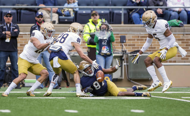 Notre Dame's Michael Young (87) tries to recover a fumble between Alohi Gilman (11), Nicco Fertitta (28) and Troy Pride Jr. (5) during the Notre Dame Blue-Gold Spring college football game Saturday, April 21, 2018, inside Notre Dame Stadium in South Bend, Ind. (Robert Franklin/South Bend Tribune via AP)