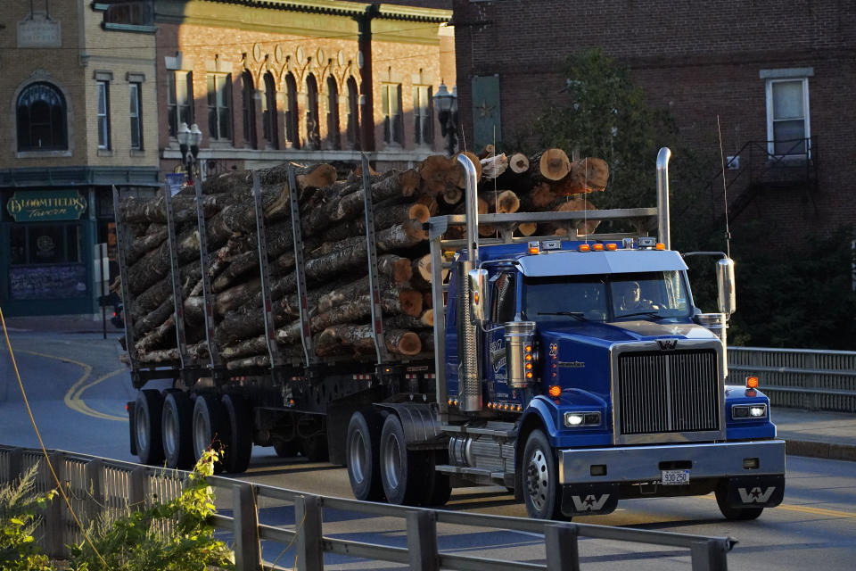 A log trucks rolls through Skowhegan, Maine, Tuesday, Sept. 14, 2021. The town that has relied on waterpower for its milling industries since the nineteenth century. (AP Photo/Robert F. Bukaty)