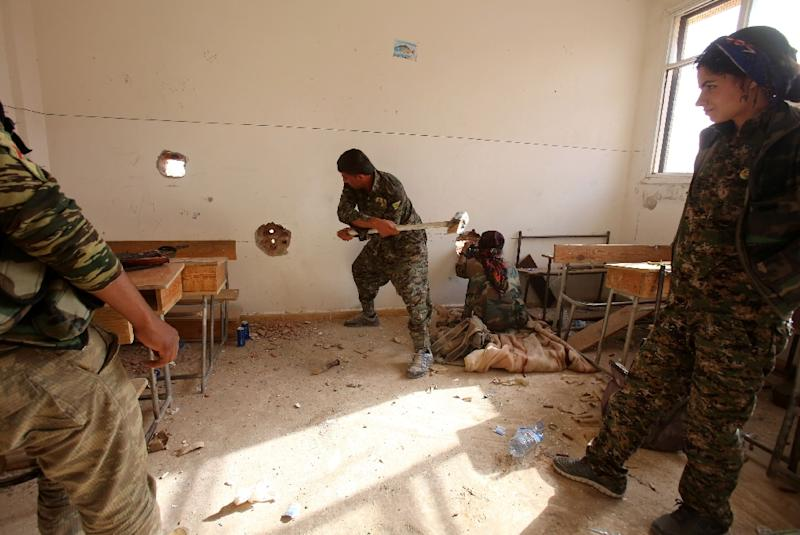 Members of the Kurdish People's Protection Units (YPG) set up a position in a classroom in the village of Maarouf in the northeastern Syrian province of Hasakeh on July 16, 2015, as they battle Islamic State group jihadists (AFP Photo/Youssef Karwashan)