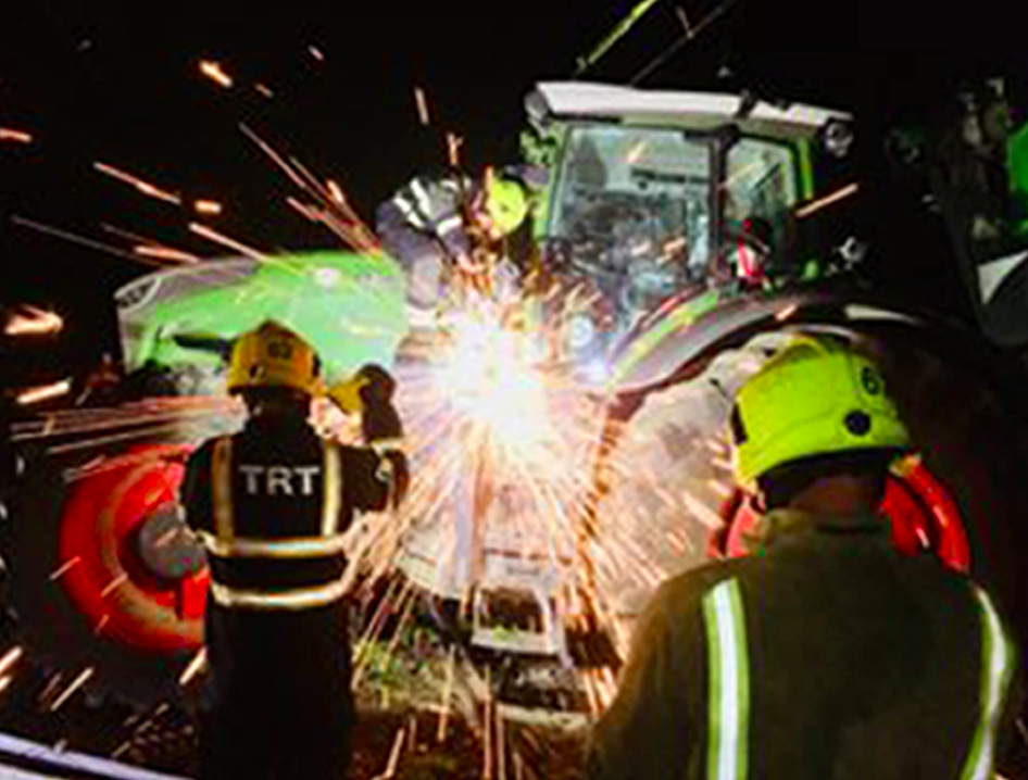 <em>Fire fighters get to work removing the tree and the tractor from the line (PA)</em>