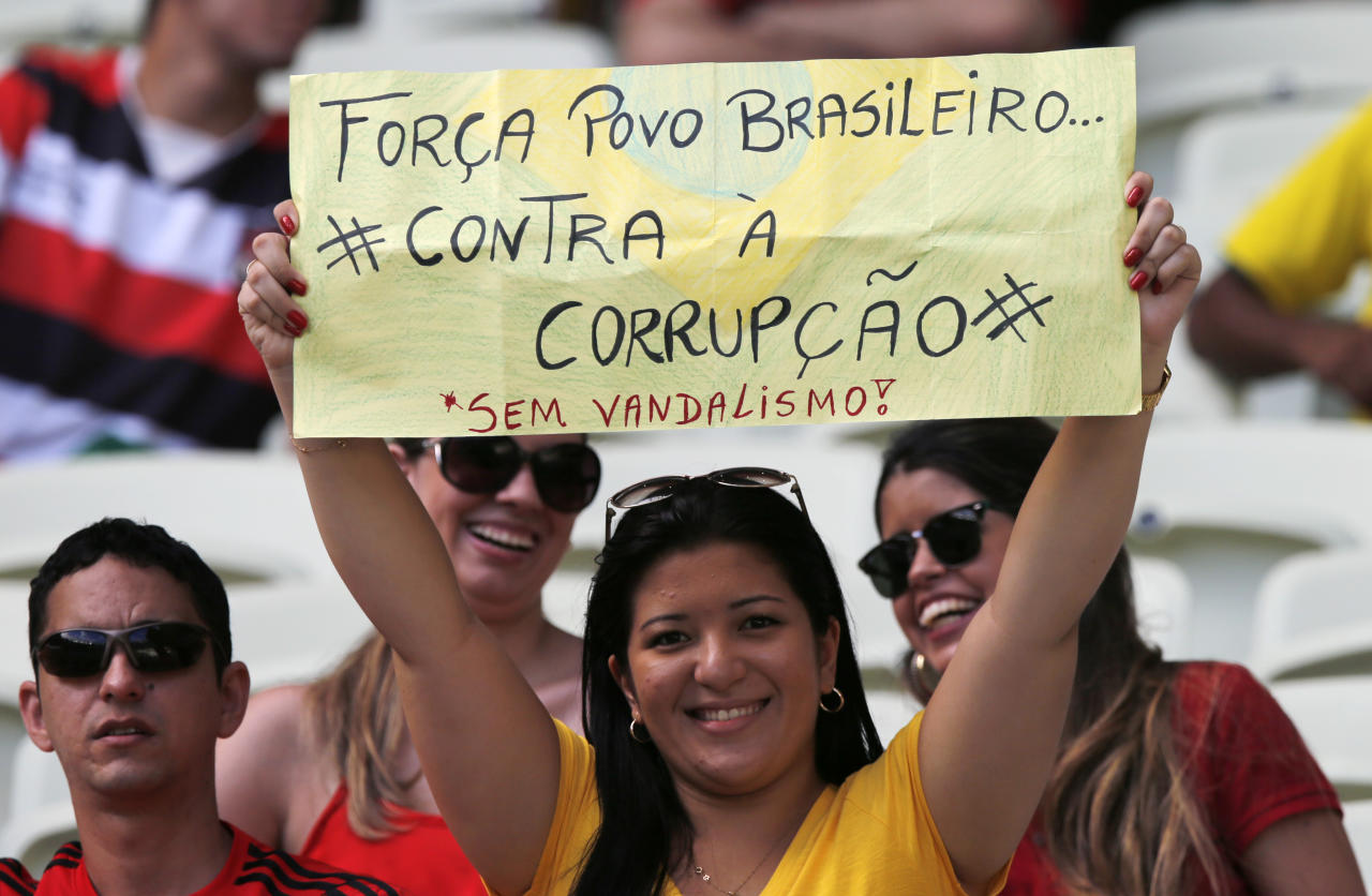 "A spectator holds a sign ""Be strong Brazilian people - against corruption - without vandalism"" prior to the soccer Confederations Cup group B match between Nigeria and Spain at the Castelao stadium in Fortaleza, Brazil, Sunday, June 23, 2013. (AP Photo/Fernando Llano)"