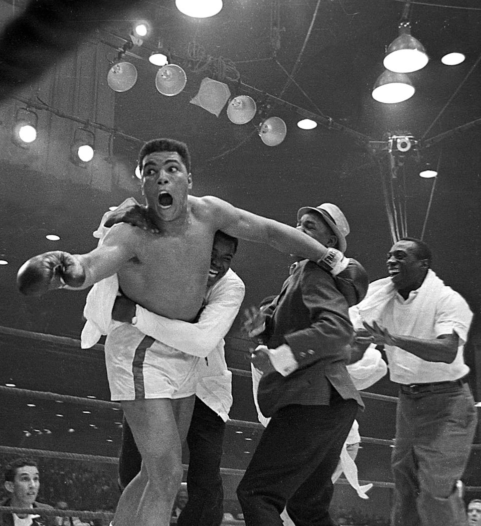 Muhammad Ali, then known as Cassius Clay, celebrates after winning the heavyweight championship with a knockout of Sonny Liston in the seventh round on Feb. 25, 1964, in Miami Beach, Fla.