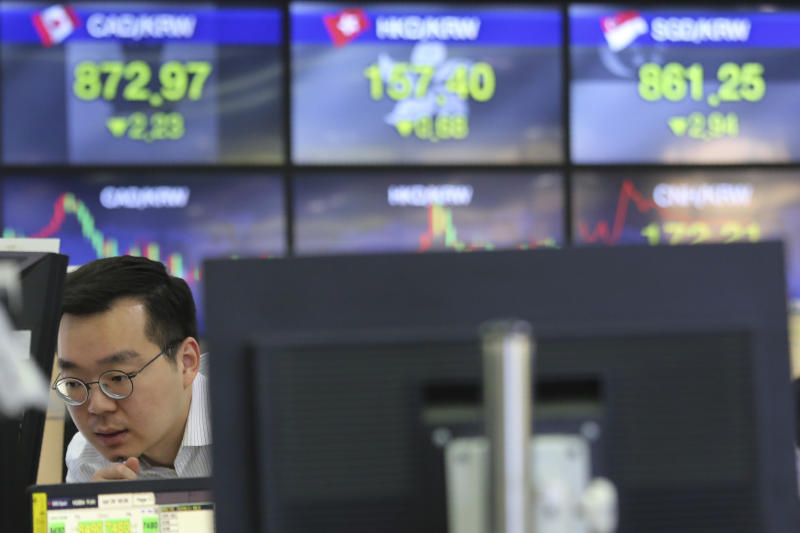 A currency trader watches monitors at the foreign exchange dealing room of the KEB Hana Bank headquarters in Seoul, South Korea, Wednesday, April 29, 2020. Asian stock markets gained Wednesday after France and Spain joined governments that plan to ease anti-virus controls and allow businesses to reopen. (AP Photo/Ahn Young-joon)
