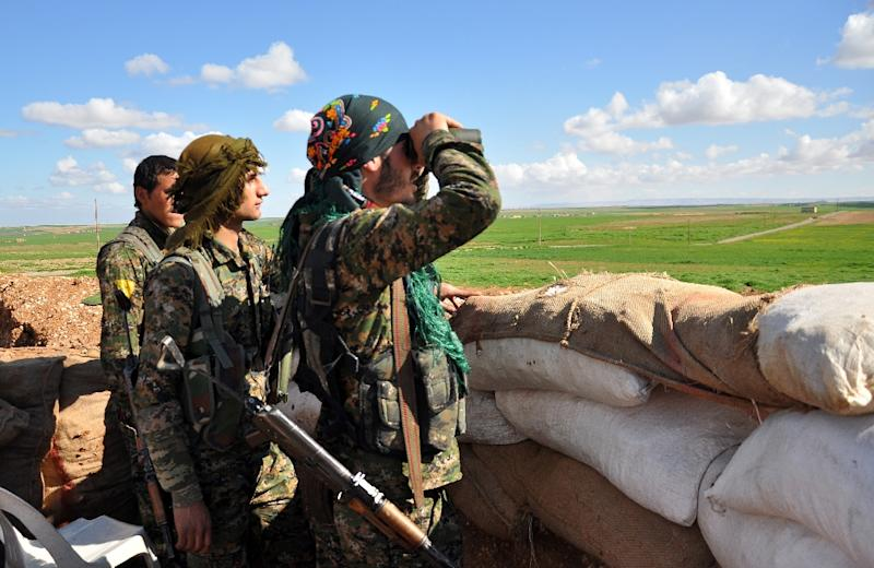 Members of the Kurdish People's Protection Units (YPG) monitor the positions of Islamic State (IS) group in the Syrian town of Ras al-Ain, close to the Turkish border on March 13, 2015 (AFP Photo/Delil Souleiman)