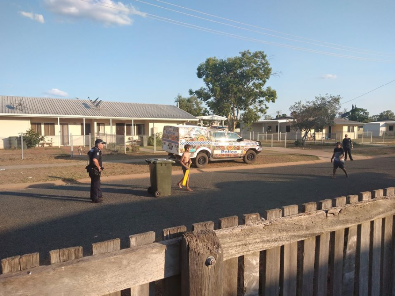 Two Queensland police officers playing cricket with two children on the road.