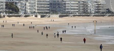 x88125038_People-walk-on-the-beach-of-La-Baule-as-France-softens-its-strict-