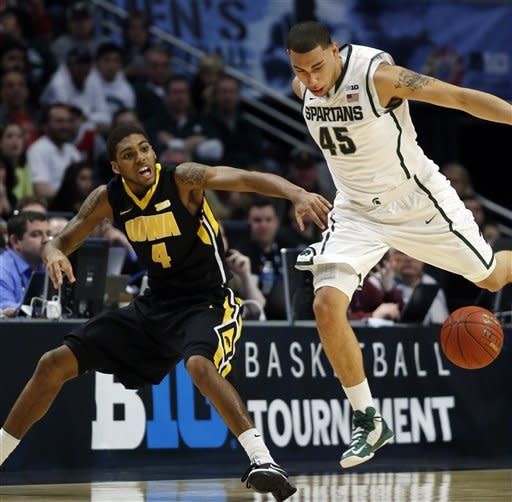 Michigan State's Denzel Valentine (45) and Roy Devyn Marble (4) go after a loose ball during the first half of an NCAA college basketball game at the Big Ten tournament Friday, March 15, 2013, in Chicago. (AP Photo/Charles Rex Arbogast)