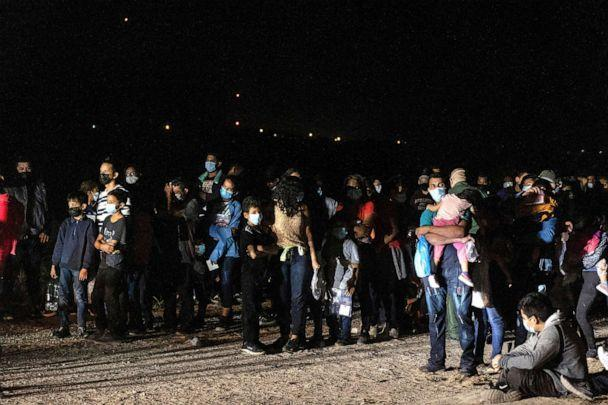 PHOTO: Asylum-seeking migrant families from Central America wait to be processed by the U.S. Border Patrol agents after crossing the Rio Grande river into the United States from Mexico in Roma, Texas, July 30, 2021. (Go Nakamura/Reuters)