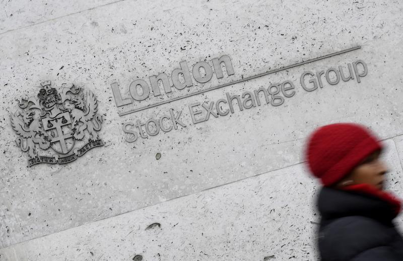 A woman walks past the London Stock Exchange building in the City of London, Britain