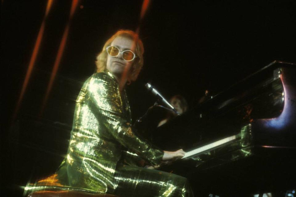 <p>Elton John's green sparkle suit radiates off the lights, while performing on stage in 1973. </p>