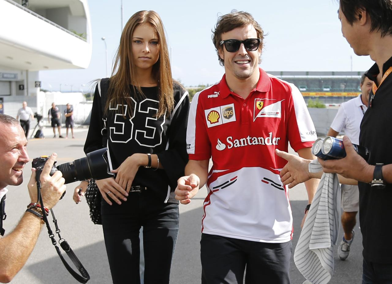 Ferrari Formula One driver Fernando Alonso of Spain (2nd R) walks with his girlfriend Dasha Kapustina as they arrive at the Suzuka circuit October 10, 2013, ahead of Sunday's Japanese F1 Grand Prix. REUTERS/Toru Hanai (JAPAN - Tags: SPORT MOTORSPORT F1)