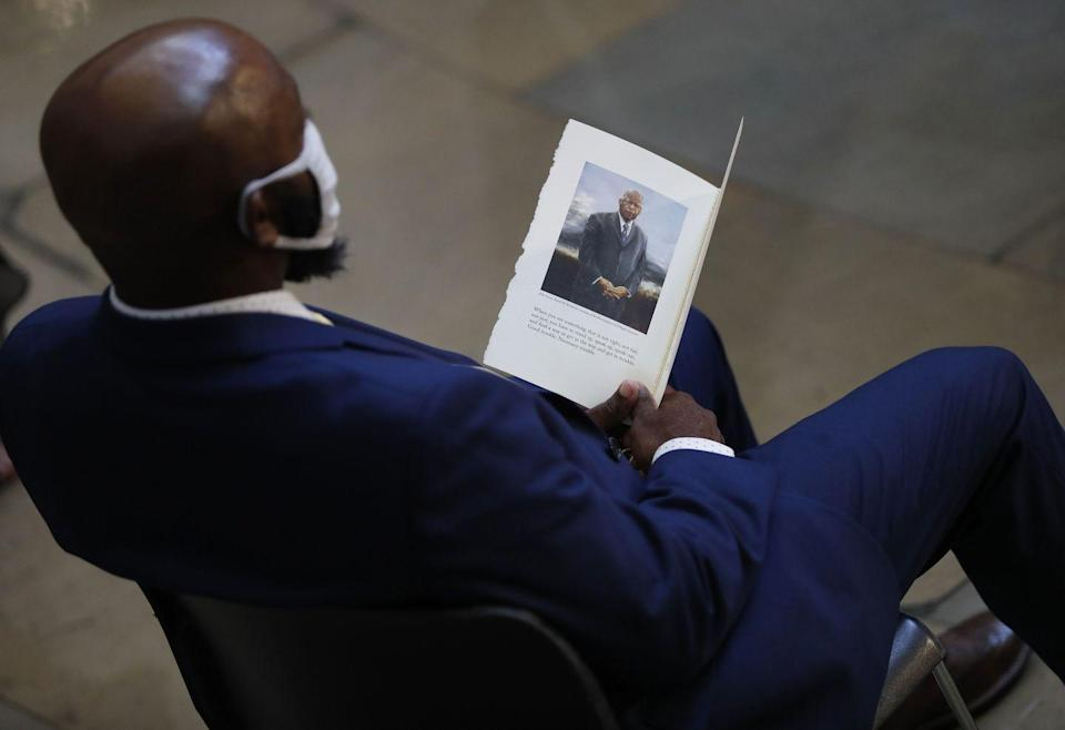 <p>An attendee views the program during the memorial service for Rep. John Lewis, D-GA, as he lies in state in the Rotunda of the US Capitol in Washington, DC, on July 27, 2020.</p>