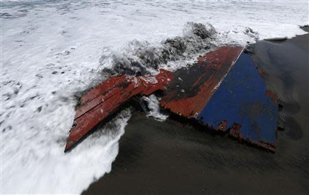 Waves wash over a piece of wreckage of a boat which sank, on Agrabinta beach on the outskirts of Sukabumi