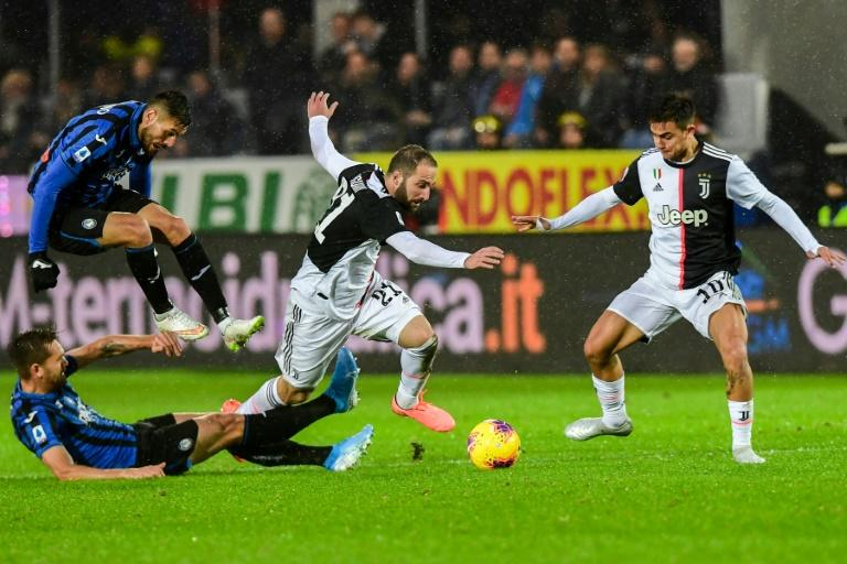 Argentine forwards Gonzalo Higuain (C) and Paulo Dybala (R) scored in the final quarter of an hour to guide Juve to a 3-1 win at Atalanta