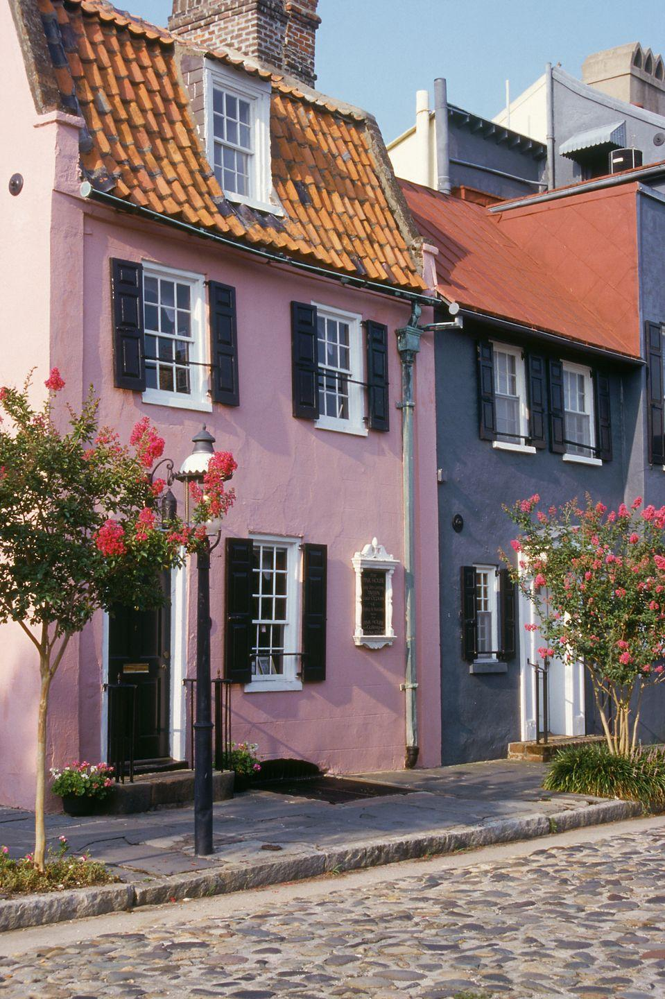 <p>A quaint cobblestone street with a pretty pink home.</p>