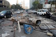Cars drive past near debris at a site of protest that happened yesterday over deteriorating economic situation