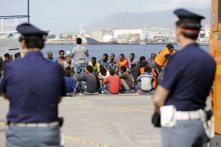 Migrants are disembarked from the Migrant Offshore Aid Station (MOAS) ship MV Phoenix in the Sicilian harbour of Messina