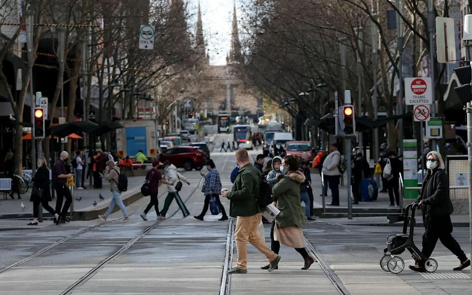 People cross the road in Melbourne, Australia on 28 July 2021, as the city's coronavirus lockdown was lifted - Con Chronis/AFP