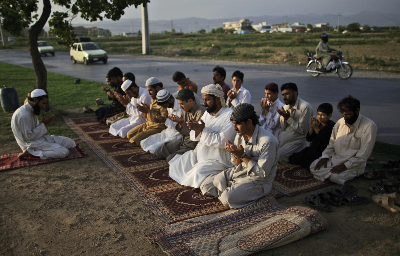 Pakistani workers chant after attending the daily Asr prayer, the afternoon prayer, on a street median a day before the start of the Muslim holy fasting month of Ramadan, on the outskirts of Islamabad, Pakistan, Friday, July 20, 2012. Muslims from Morocco to Afghanistan are steeling themselves for the toughest Ramadan in more than three decades with no food or drink, not even a sip of water, for 14 hours a day during the hottest time of the year. (AP Photo/Muhammed Muheisen)