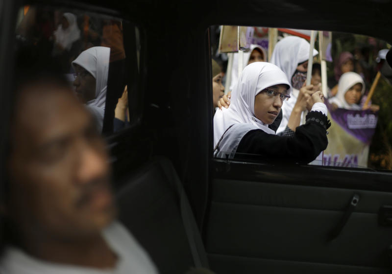 A Muslim woman takes a break during a protest demanding the cancellation of the Miss World pageant that will be held in Bali and Sentul, West Java later this month, in Jakarta, Indonesia, Thursday, Sept. 5, 2013. Hundreds of Muslims staged the rally saying that such a competition violates Islamic teachings. (AP Photo/Dita Alangkara)