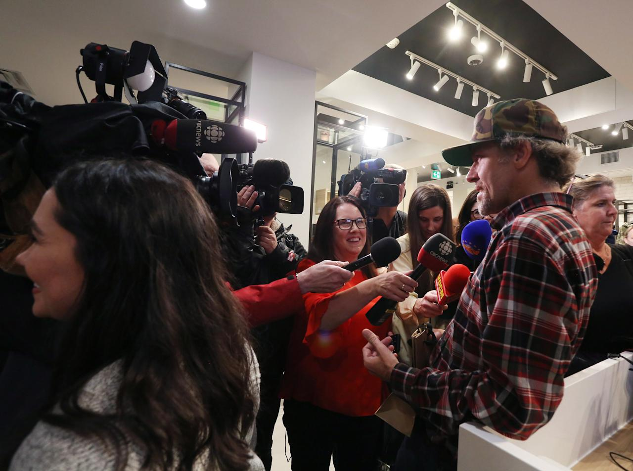 <p>Ian Power talks with the media at the Tweed shop on Water Street in St. John's N.L. following his purchase of the first legal marijuana for recreational use in Canada at 12:01am local time on Wednesday October 17, 2018.<br />(Photo from Paul Daly, The Canadian Press) </p>
