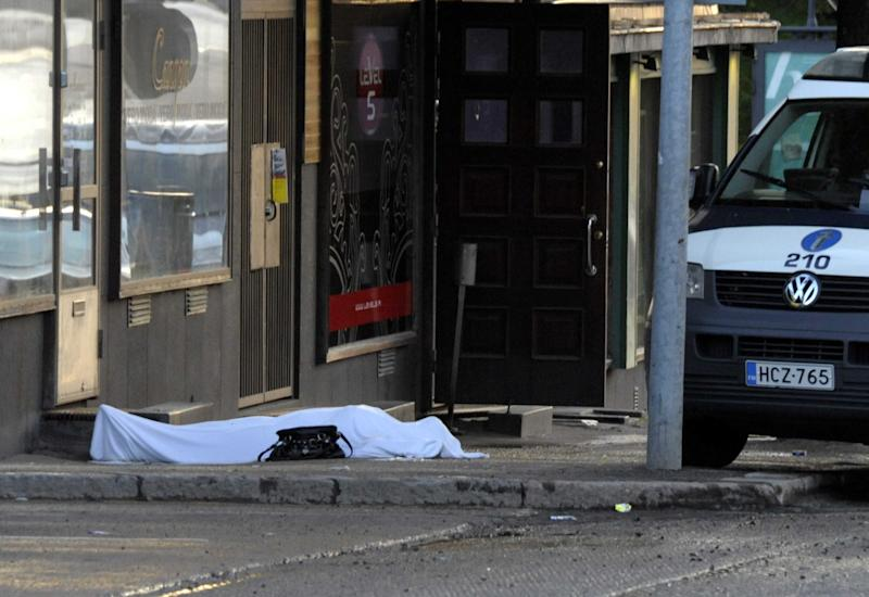 A body covered with a sheet lies on the street in Hyvinkaa, Finland, Saturday May 26, 2012. A gunman in southern Finland has killed one person and wounded eight others in what appeared to be a random shooting, police said Saturday. (AP Photo/Lehtikuva/Sari Gustafsson) FINLAND OUT