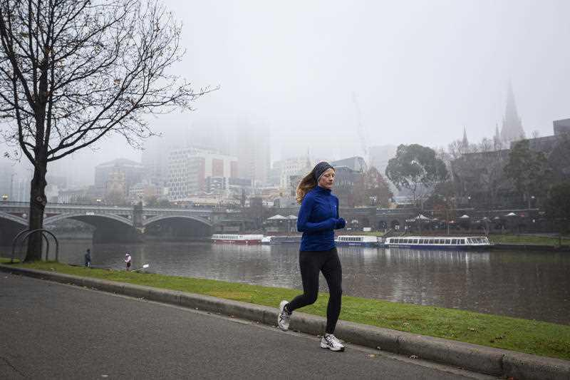 A woman is seen jogging along the Yarra River in Melbourne.