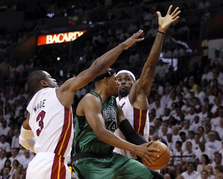 Miami Heat's Dwyane Wade (3) and Lebron James, right, defend Boston Celtics' Paul Pierce (34) during the second half of Game 1 in their NBA basketball Eastern Conference finals playoffs series, Monday, May, 28, 2012, in Miami. The Heat won 93-79. (AP Photo/Lynne Sladky)
