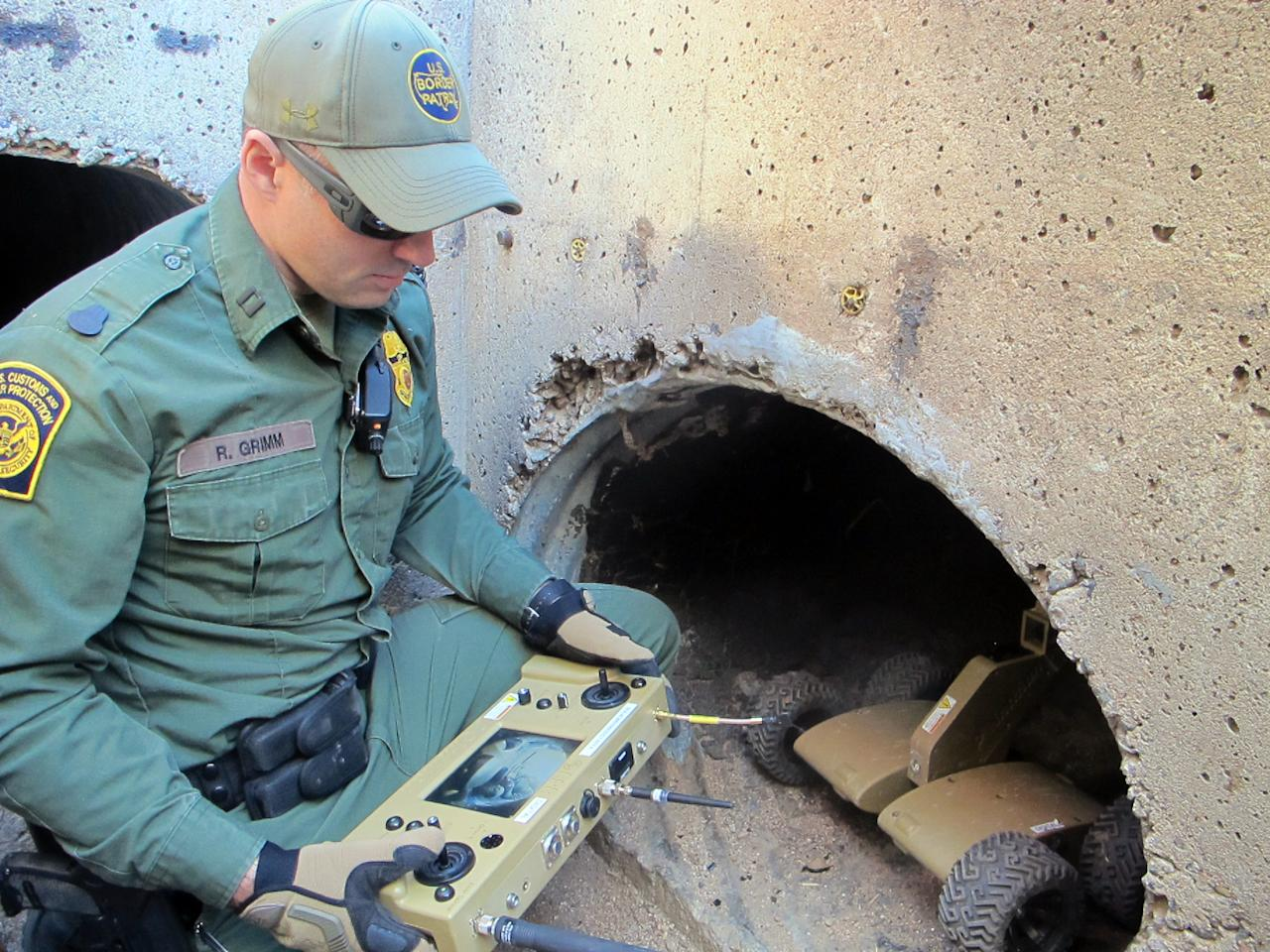 U.S. Border Patrol Agent Ryan Grimm demonstrates how a robot is used to navigate a drainage canal along the border fence during a briefing in Nogales, Ariz., Tuesday, Jan. 14, 2014. With more than 75 underground drug smuggling tunnels found along the border since 2008, mostly in California and Arizona, the Border Patrol is utilizing the wireless, camera-equipped robot, to search underground while keeping agents safer. (AP Photo/Brian Skoloff)
