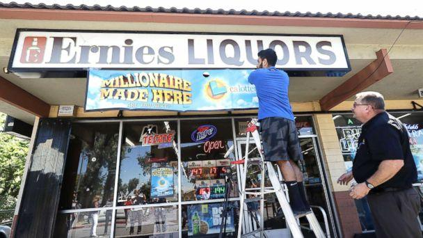 PHOTO: California Lottery official Mike Neis, right, watches as Amol Sachdev hangs a sign over his family's store Ernie's Liquors where a Mega Millions lottery ticket worth more than $500 million was sold in San Jose, Calif., July 28, 2018. (Jeff Chiu/AP)