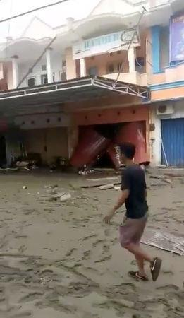 People walk near the ruins of shophouses after a tsunami hit in Palu, Indonesia Sulawesi Island, in this September 29, 2018 photo by Palang Merah Indonesia. Palang Merah Indonesia/Social Media/via REUTERS