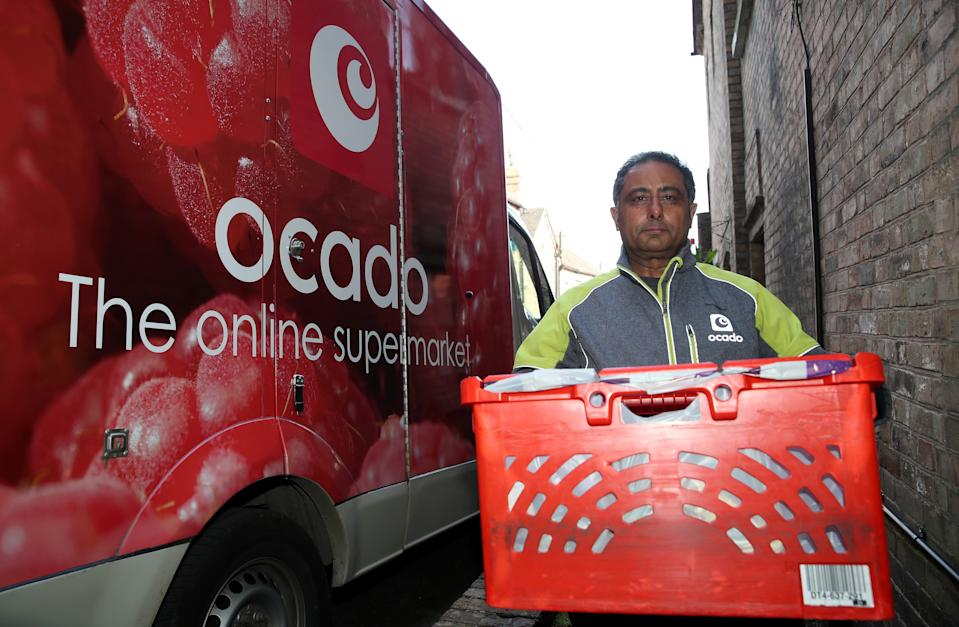 A delivery driver for Ocado online supermarket delivers a shopping order in Ironbridge, Shropshire the day after Prime Minister Boris Johnson put the UK in lockdown to help curb the spread of the coronavirus. (Photo by Nick Potts/PA Images via Getty Images)